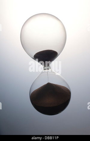 Hour glass sand timer running out of time - Stock Photo