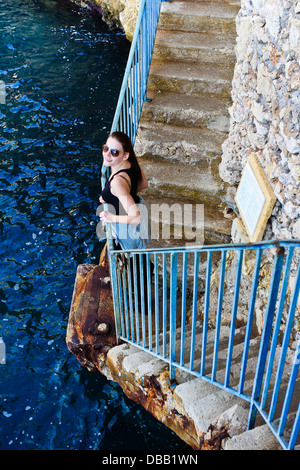 Smiling Brunette Woman Standing At A Blue Railing Next To The Sea - Stock Photo