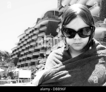 pre-teen girl, big sun glasses looking down. wet hair. towel wrapped around her shoulders. black and white. old - Stock Photo