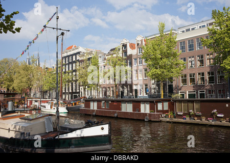 Boats and houseboats on a canal in Amsterdam, Holland, Netherlands. - Stock Photo