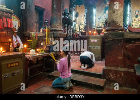Two unidentified women pray in a temple on January 2, 2008 in Ho Chi Minh City, Vietnam - Stock Photo