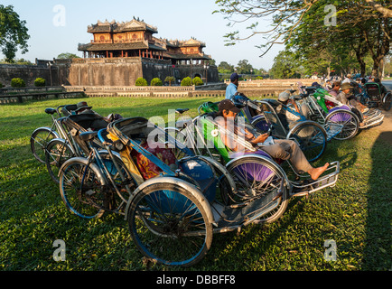 A group of unidentified cyclo drivers wait for tourists in front of the Citadel on January 10, 2008 in Hue, Vietnam - Stock Photo