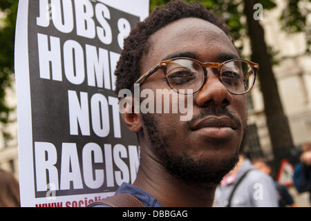London, UK. 27th July, 2013. A man demands jobs and homes, not racism during a march from the US embassy to Downing - Stock Photo