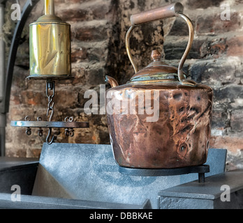 Copper kettle hanging above old stove. - Stock Photo