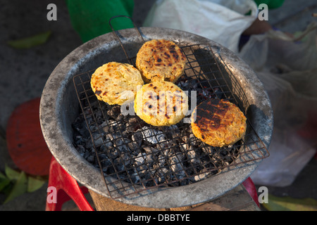 Sweet potato cakes grilling outside on street in Old Quarter, Hoi An, Quang Nam, Vietnam, Southeast Asia - Stock Photo