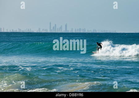 Surfer riding a wave with Surfers Paradise skyline in background. Rainbow Bay, Coolangatta, Gold Coast, Queensland, - Stock Photo