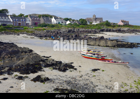 The shoreline of Iona from the ferry dock  across St Ronans Bay with a view of the houses and abbey with kayaks - Stock Photo