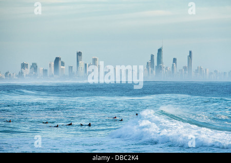 Surfers in morning swell with Surfers Paradise skyline in background. Burleigh Heads, Gold Coast, Queensland, Australia - Stock Photo