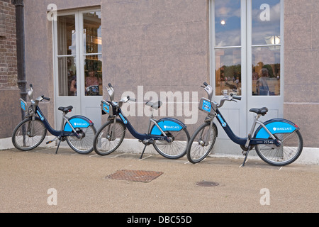 3 Boris bikes parked outside Kensington Palace in London - Stock Photo