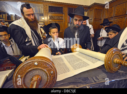 Religious Jews pray in the Rebbe's study at Lubavitch Headquarters in Brooklyn, New York. Bar Mitzvah boy called - Stock Photo