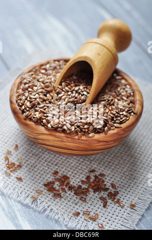 Flax seeds in wooden bowl on wooden background - Stock Photo