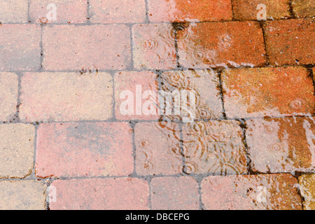 Heavy Raindrops Splashing On Rustic Red Brick Patio Paving In UK Garden  With Porous Joints Acting