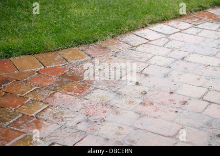 Background And Texture; Heavy Raindrops Splashing On Rustic Red Brick Patio  Paving In UK Garden With Porous Joints Acting