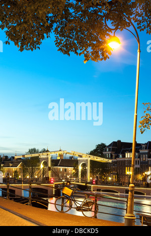 Amsterdam Magere Brug Skinny Bridge on the Amstel River dusk night evening in summer. A single bicycle is locked - Stock Photo
