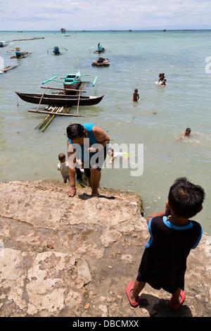 Young local Children enjoying a Bath in the Ocean in Tagbilaran on Bohol Island, Philippines - Stock Photo
