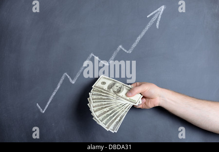 growth chart with a hand full of dollar bills - Stock Photo