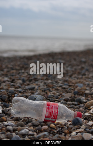 Litter on the rocky stone beach showing a empty discarded Coca Cola bottle. - Stock Photo