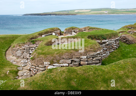 Skara Brae Neolithic Village on Mainland Orkney with the Bay of Skaill in the background. - Stock Photo