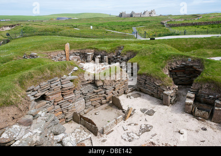 House 5 at Skara Brae Neolithic Village on Mainland Orkney with Skaill House in the background. - Stock Photo