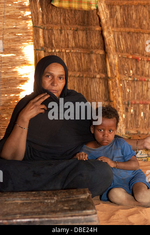 Inside Tuareg tent made from woven mats. The village 'queen'  in the home of her married daughter with her grand - Stock Photo