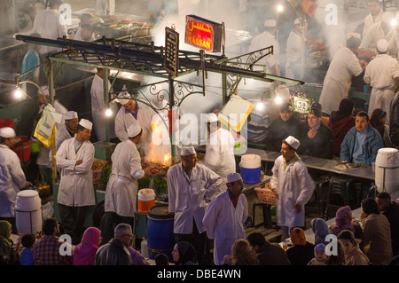 Overlooking an alfresco food stall showing cooks surrounding a smoky cooking fire, in Djemaa el-Fna square at night, - Stock Photo