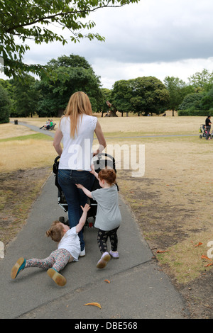 Young mum with twin girls and one is having a temper tantrum. - Stock Photo