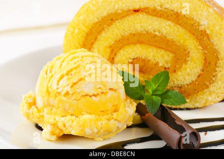Slice of Swiss roll with yellow ice cream and chocolate sauce - Stock Photo