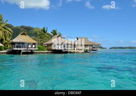Luxury thatched roof honeymoon bungalows in a vacation resort in the clear blue lagoon of the tropical island of - Stock Photo