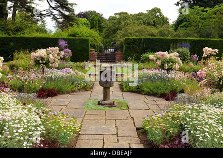 Flagged garden with a stone vase ornament and summer flowers. - Stock Photo