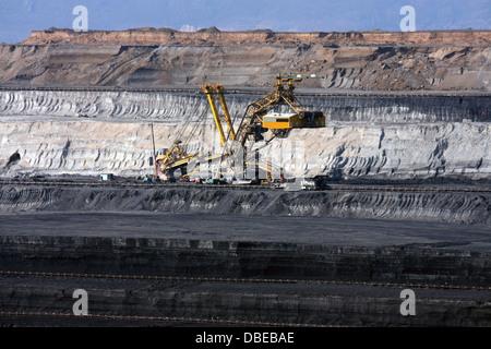 huge and deep coal mine with excavator machine in europe - Stock Photo