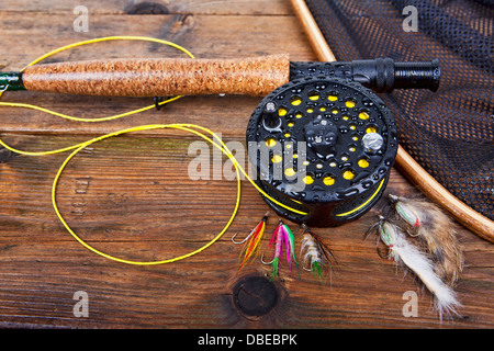 fly fishing rod and reel on a wet wooden background, focus on the reel. - Stock Photo