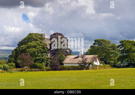 St.Marys Church and Thatched cottage at  Bratton Clovelly in West Devon under a stormy sky with Dartmoor in the - Stock Photo