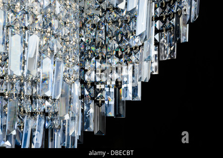 Contemporary glass chandelier crystal isolated over black background - Stock Photo
