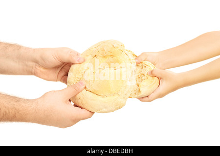 Man and child breaking apart a bread loaf - Stock Photo