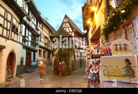Girl taking a picture at the typical timber framing houses. Eguisheim. Wine route. Haut-Rhin. Alsace. France - Stock Photo