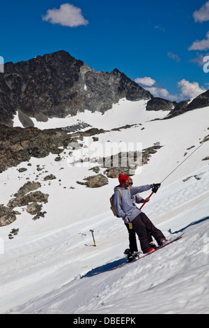 Two snowboarders on a Tee-bar on Blackcomb Mountain in mid-summer - Stock Photo