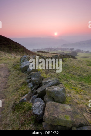A typical Yorkshire dry stone wall leading the eye down towards a misty valley - Stock Photo