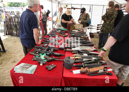 People looking at guns at a Military and Arms Fair - Stock Photo