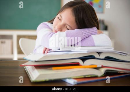 Mixed race girl sleeping on books in class - Stock Photo