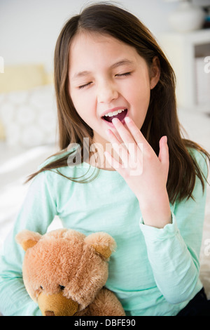 Mixed race girl with teddy bear yawning - Stock Photo
