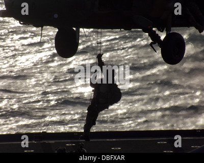 An Australian army soldier from the 2nd Commando Regiment, Domestic Counter Terrorism fast-rappels from a S-70A - Stock Photo