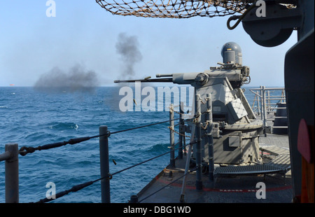 A Mark 38 25 mm machine gun fires rounds during a live-fire exercise aboard the guided missile cruiser USS Monterey - Stock Photo