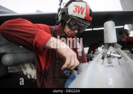 U.S. Navy Aviation Ordnanceman 3rd Class Branden Samela attaches a training bomb to a bomb rack on an F/A-18C Hornet - Stock Photo