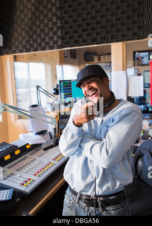 Mixed race disc jockey smiling in studio - Stock Photo