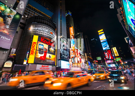Traffic in Times Square at night with taxi cabs driving through the streets, New York City - Stock Photo