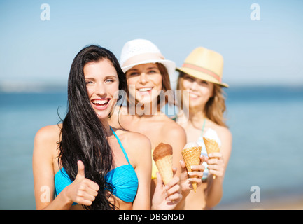 girls in bikini with ice cream on the beach - Stock Photo