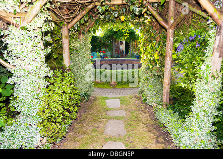 Typical English garden Arbour Arch archway Canopy tunnel leading in to garden - Stock Photo