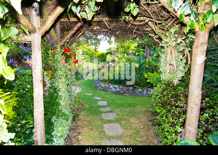 Typical English garden Arbour Arch archway Canopy leading in to garden - Stock Photo