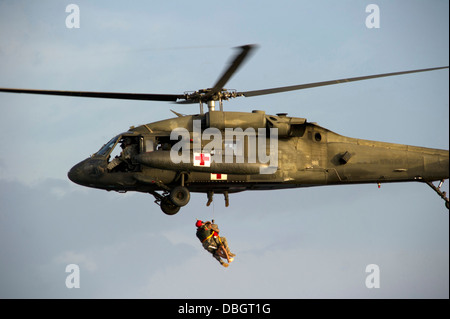 A US Army Flight Medic retrieves a Green Beret special forces soldier using a hoist to a UH-60 Blackhawk helicopter - Stock Photo