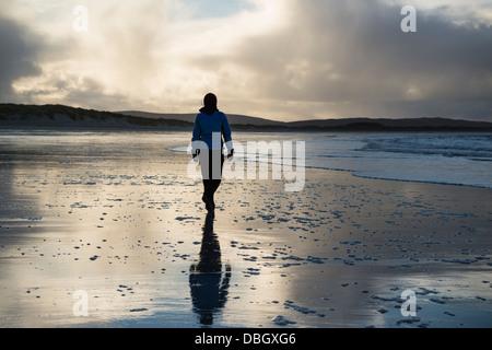 Woman walks on Traigh Hornais beach, North Uist, Outer Hebrides, Scotland - Stock Photo